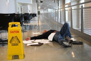 Man lies on the wet floor on which he slipped in spite of caution sign selective focus on man's chin